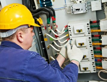 tradesman working on electrical system in ppe