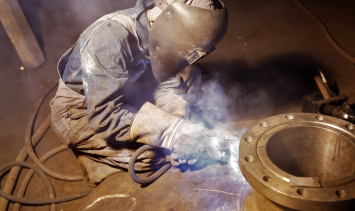 Man welding in a crouched position with welding helmet