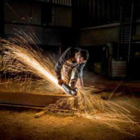 Man using angle grinder and Klingspor abrasive disk to cut railway sleeper