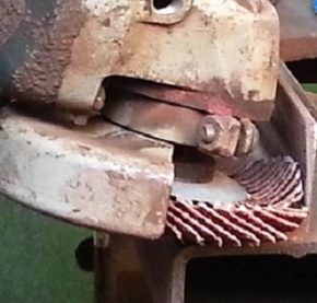 Close up of flap disc being used against steel beam